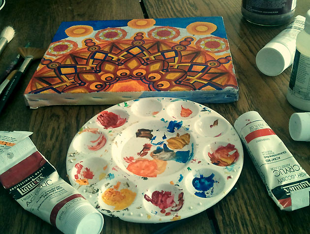 red orange navy and yellow sunburst painting with art supplies