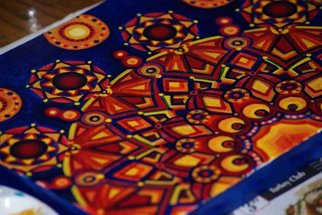 red yellow orange and blue kaleidoscope like acrylic sunburst painting