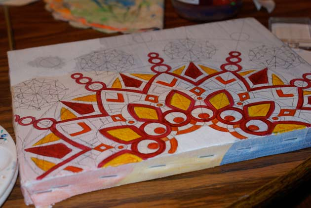 beginning of sunburst painting with red and yellow colored in